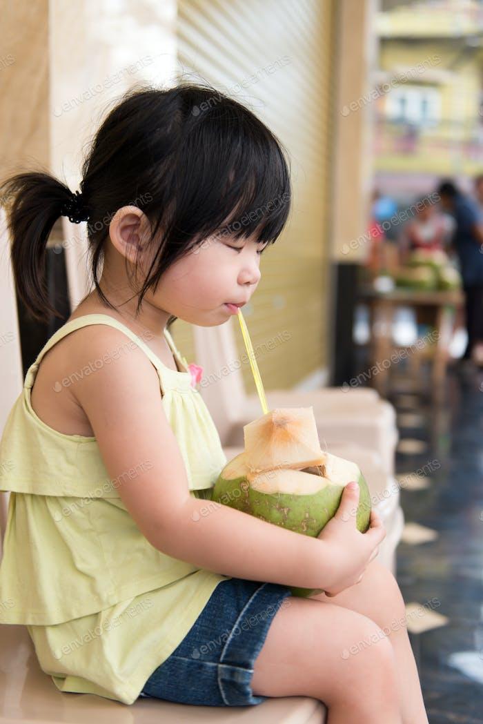 Cute girl drinking coconut water