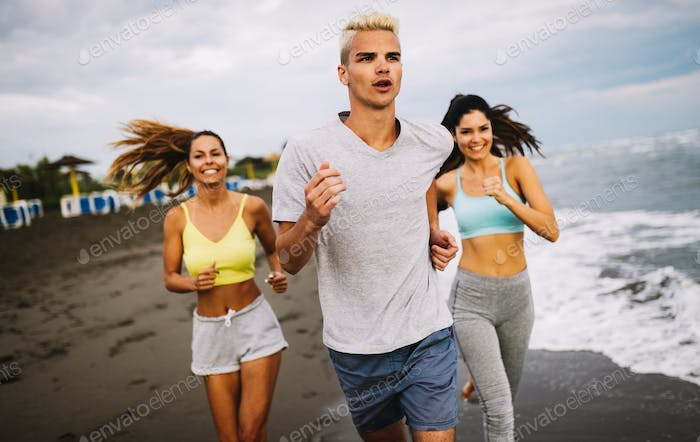 Group of sport people running on the beach