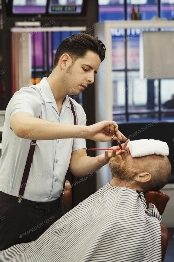 A customer sitting in the barber's chair, with a hot towel on his face, and a barber trimming his