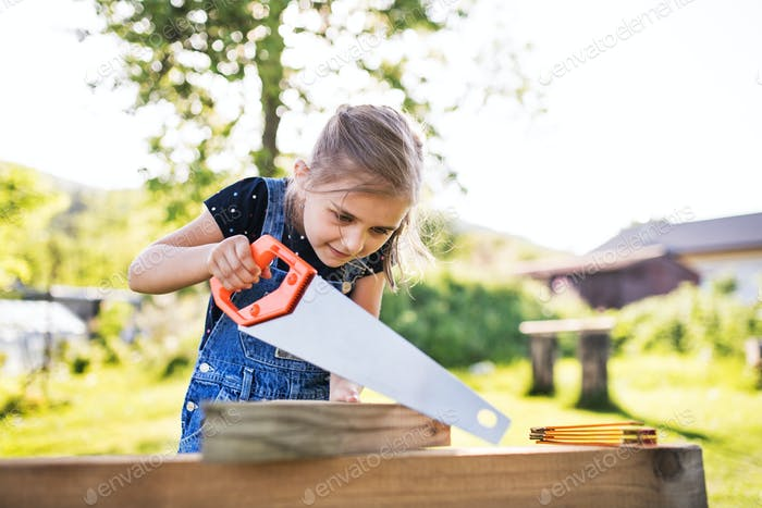 A small girl with a saw outside, making a wooden birdhouse.