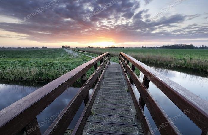 bridge via river at beautiful sunrise