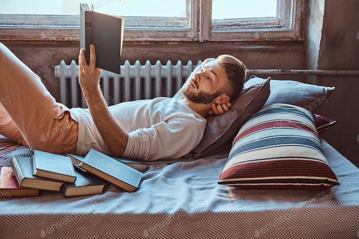 Porträt eines gutaussehenden Studenten, der ein Buch in seinem Bett liest. Bildungskonzept.