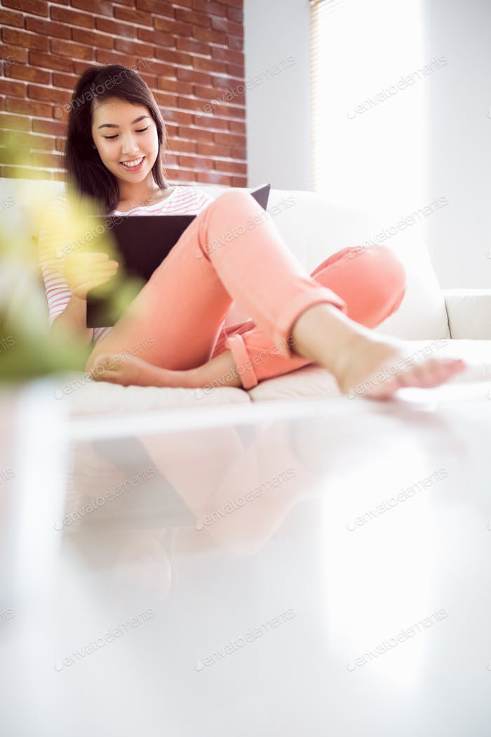 Smiling asian woman on couch reading at home in the living room