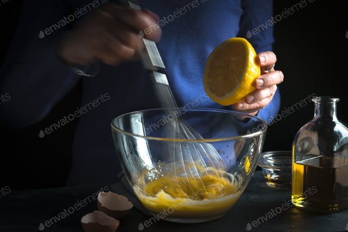 Whipping yolk with mustard and squeezing lemon juice
