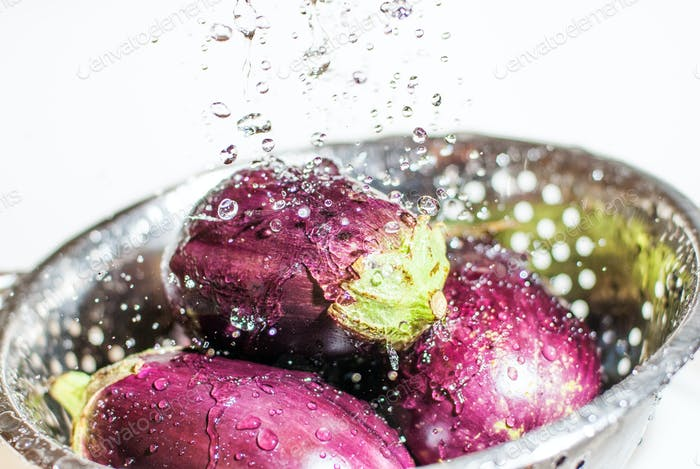 Eggplants being washed in colander under tap fresh water