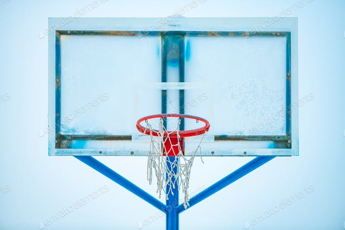 Frozen outdoor basketball hoop in winter snow