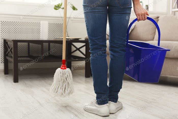 Unrecognizable woman with mop ready to clean floor