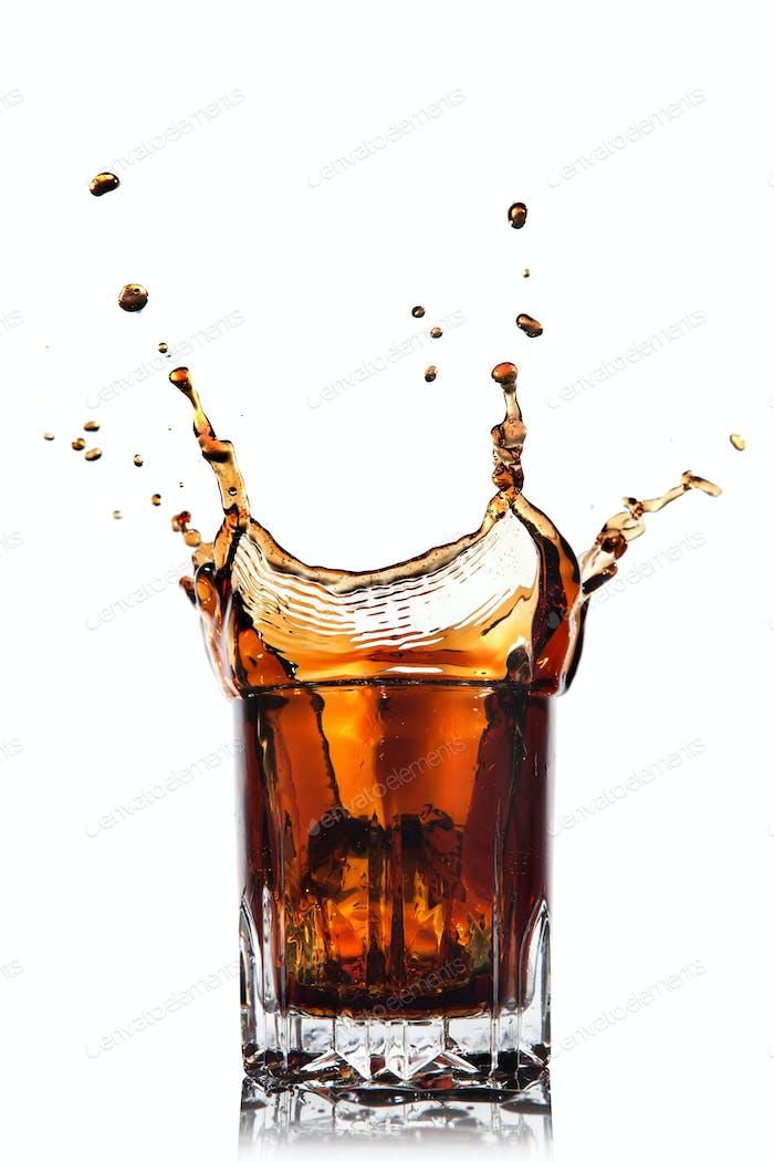 Splash Cola in Glas isoliert auf weiß