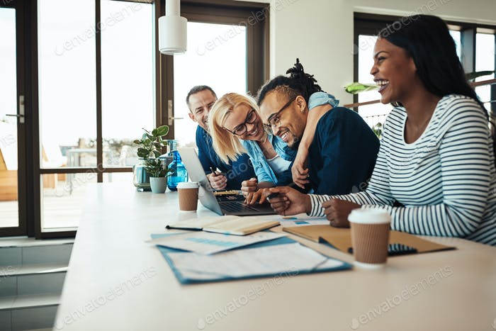 Two laughing businesspeople sitting with colleagues during an office meeting