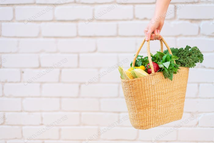 Girl holding straw basket with healthy organic vegetables, brick background, copy space. Autumn