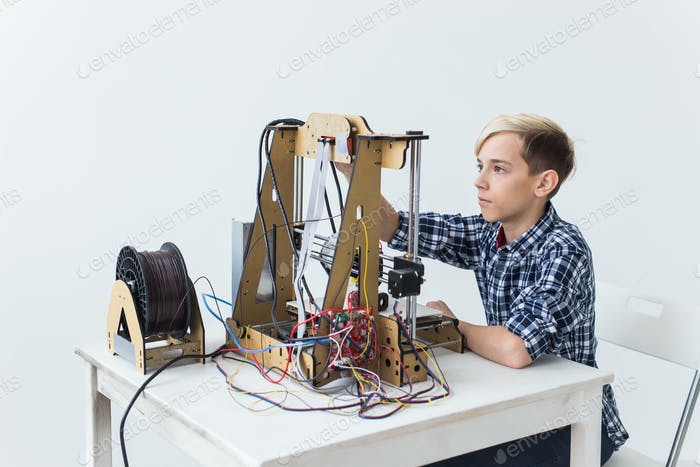 Education, children, technology concept - teen boy is printing on 3d printer