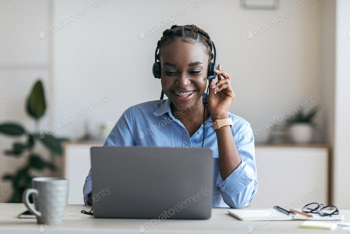 Black female manager wearing headset and using laptop in office, consulting client