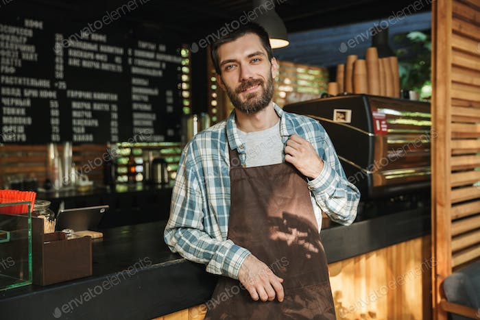 Portrait of happy barista guy working in street cafe or coffeeho
