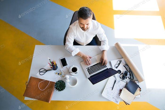 Geschäftsmann am Schreibtisch mit Laptop in seinem Büro.