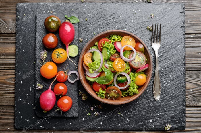 Top view at vegetable salad of lettuce, cherry tomatoes, radish,