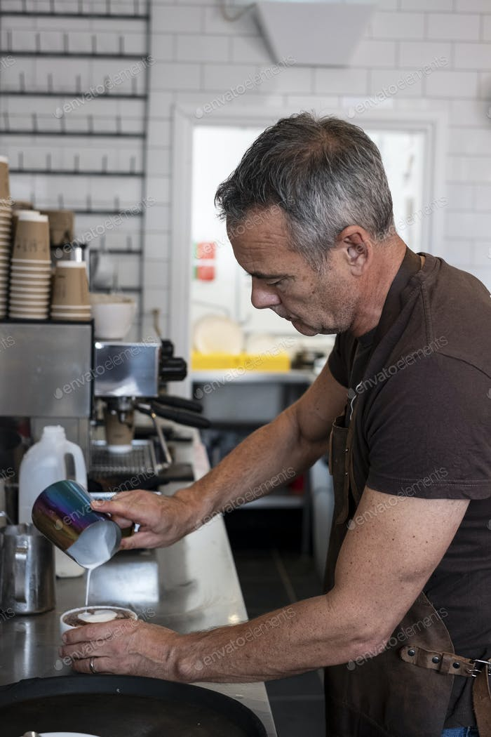 Male barista wearing brown apron, standing at espresso machine, pouring milk.