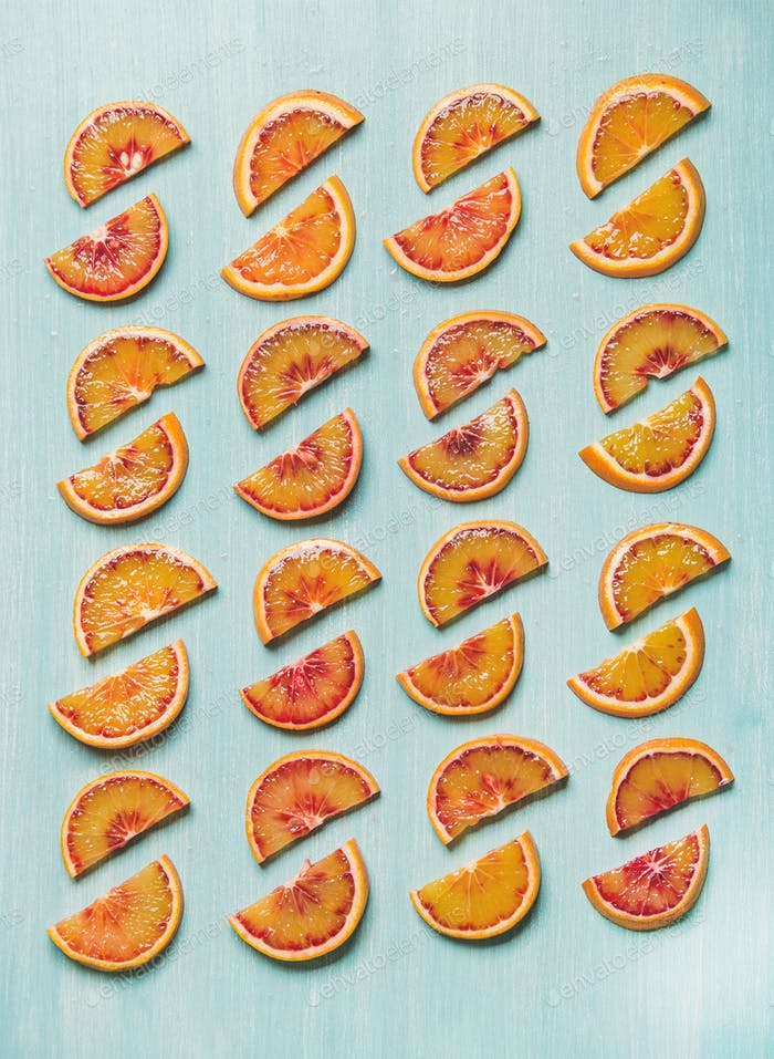 Fresh juicy blood orange slices placed in rows, blue background