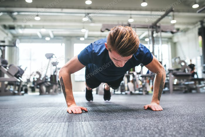 Young fit man in gym doing push ups.
