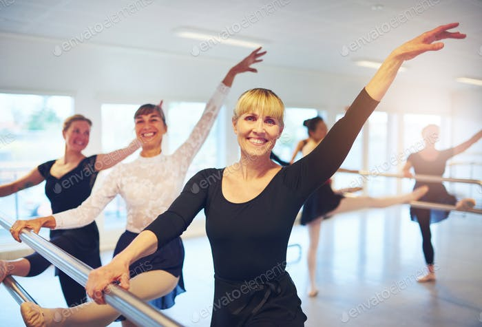 Group of mature ballet dancers looking at camera in class