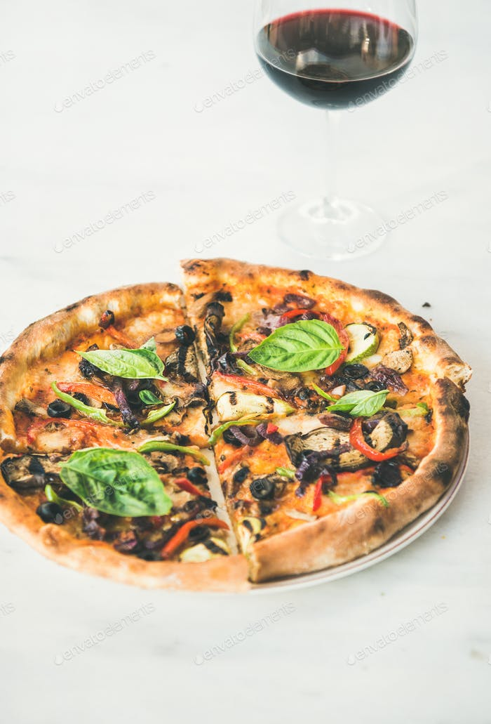 Freshly baked pizza with vegetables, basil and glass of wine