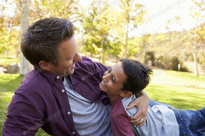 Vater und Sohn liegend in einem Park umarmen