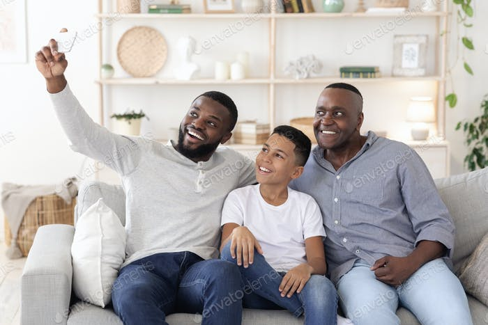 Smiling black father, son and grandfather sitting on couch and taking selfie