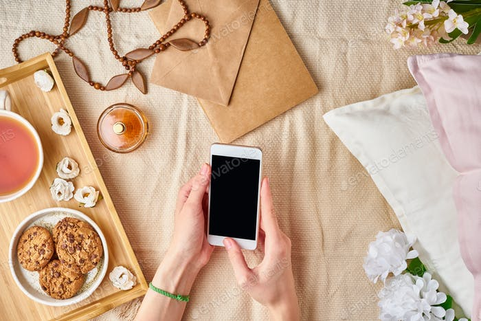 Flatlay women's hands holding a smartphone. Cozy home rest, vacation, weekend.