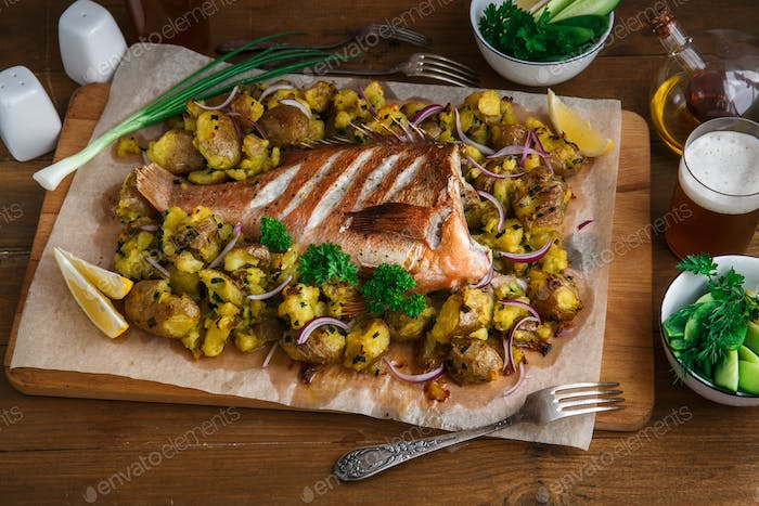 Red sea perch or red grouper baked with potatoes, top view