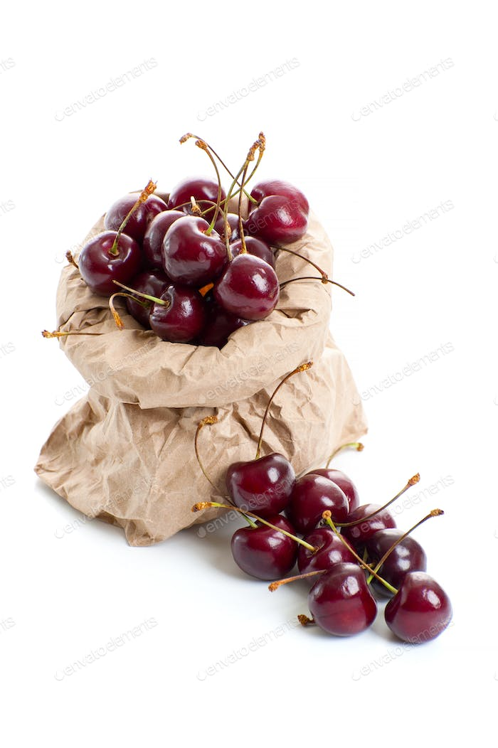 Ripe red cherry in a paper bag on a clean white background.