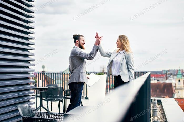 Zwei junge Geschäftsleute stehen auf einer Terrasse außerhalb des Büros, Ausdruck Aufregung