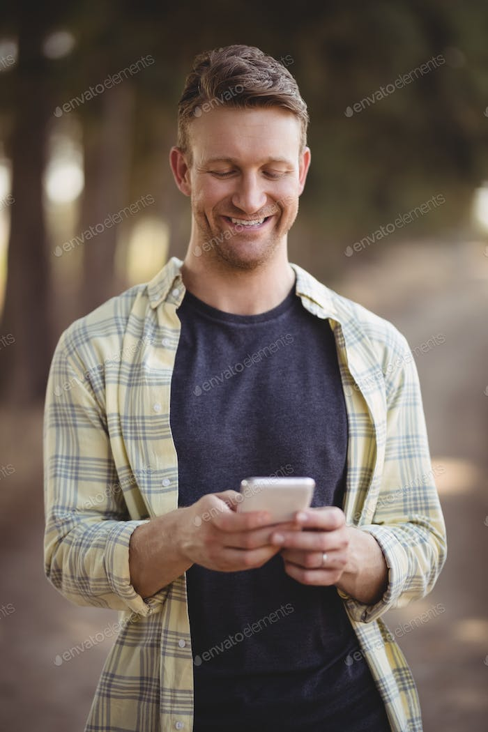 Smiling man using mobile phone at olive farm