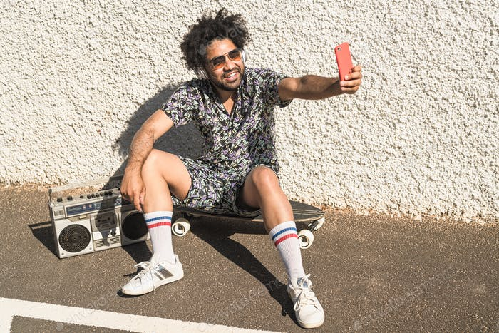 Young Afro man taking selfie with mobile phone while listening music with headphones and boombox