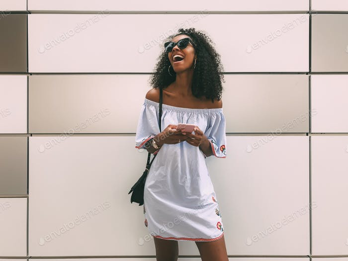 Cheerful black woman with mobile phone