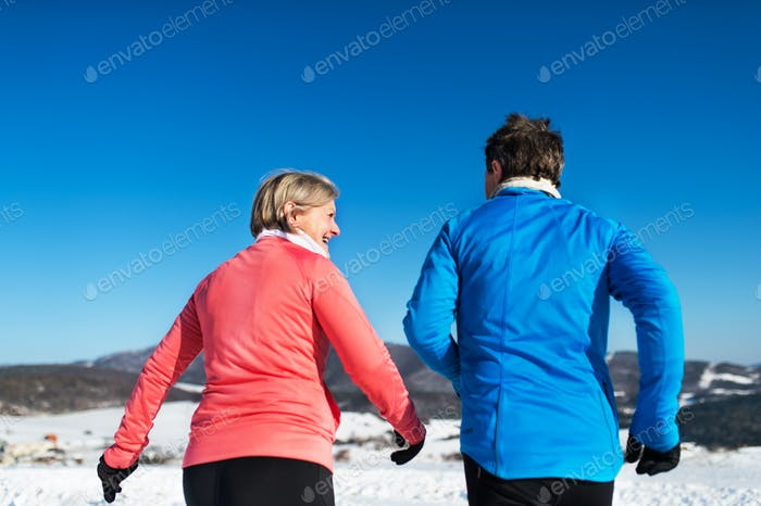 Rear view of senior couple jogging in winter nature.