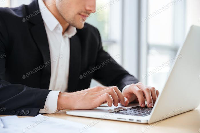 Businessman sitting and using laptop in office