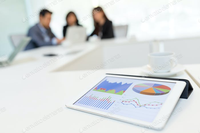 Digital tablet showing graph with business partners discussing in meeting room