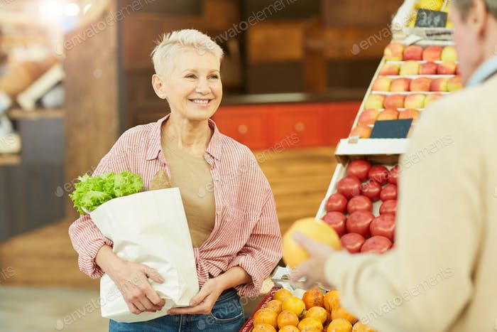 Smiling Adult Woman Buying Vegetables at Farmers Market