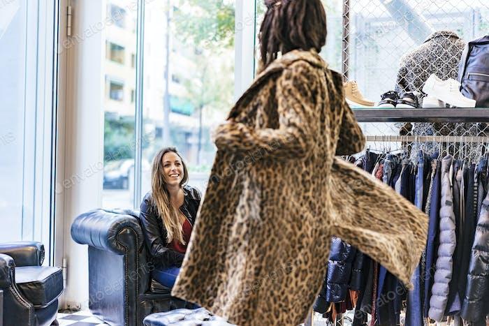 zwei gemischte Rennen weibliche Freunde kaufen Kleidung in einem Geschäft und Spaß haben