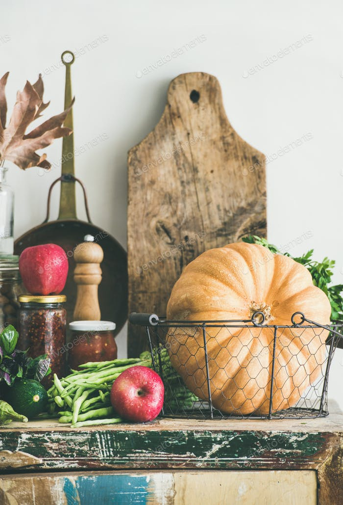 Autumn food ingredients and utensils over cupboard chest, vertical composition