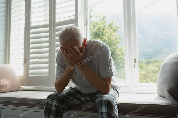 Front view of active senior Caucasian man covering face with hands on window seat in bedroom at home