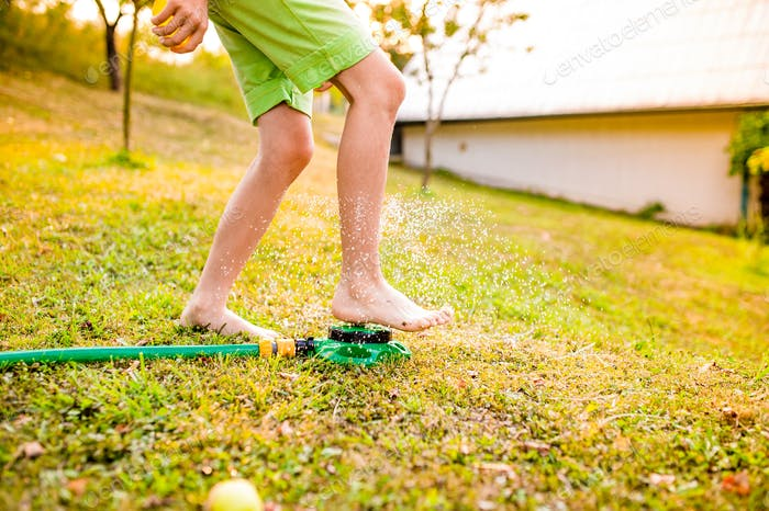 Legs of a boy in garden at the sprinkler