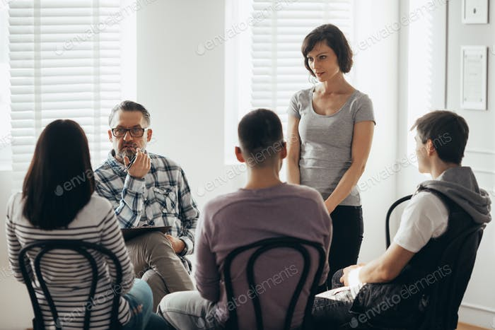 woman stands in front of a group of people during a therapy meeting