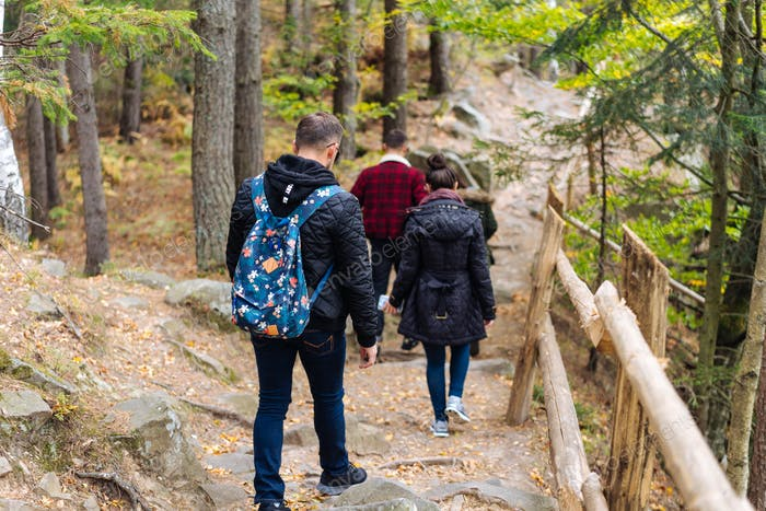 man and woman walking along hiking trail