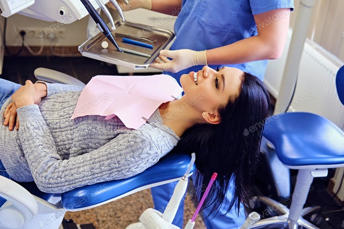 Dentist examining female's teeth in dentistry.