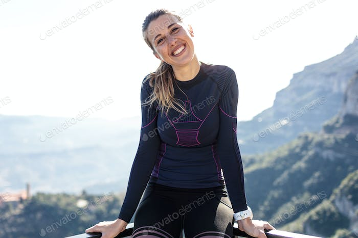 Sporty young woman looking at the camera on the mountain peak.