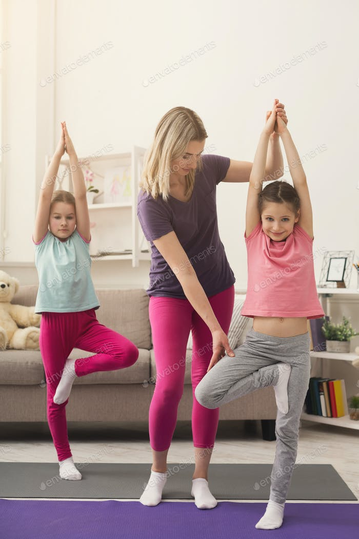 Young woman and daughters doing yoga exercise at home