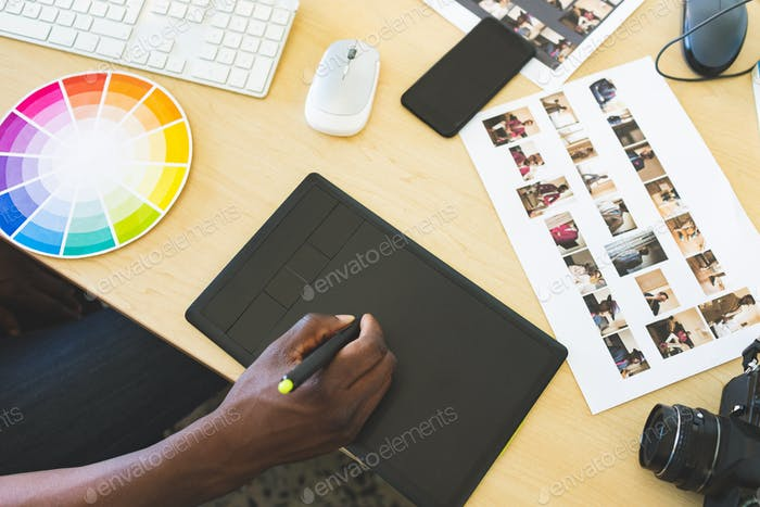 High angle view of young African-American businessman working on graphic tablet in office