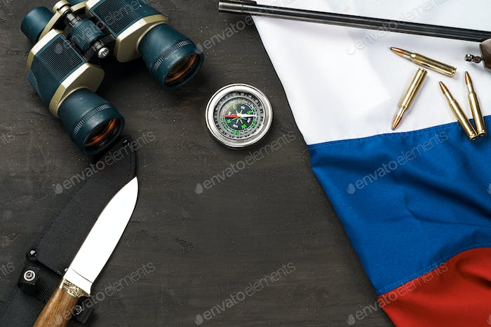 Hunting knife, binoculars and cartridges with russian flag on black background