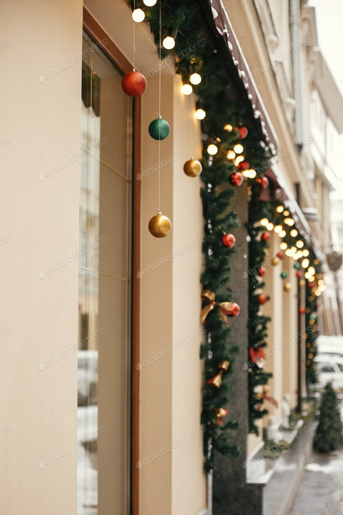Stylish christmas fir branches with golden lights and colorful festive baubles in store window