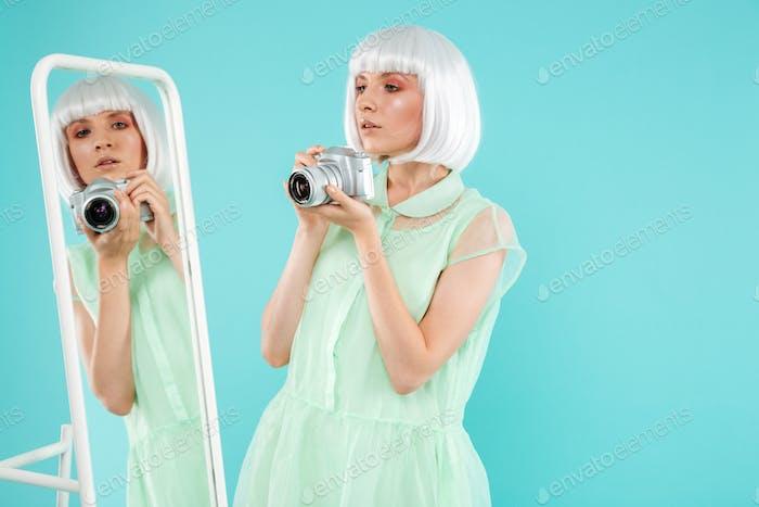 Ziemlich junge Frau nehmen selfie mit Spiegel und Fotokamera